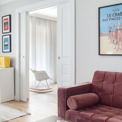 Salón de vivienda en Madrid. Espacios conectados a través de puertas correderas. Sofá de terciopelo rosa con capitoné. Cuarto infantil y zona de juegos. Mecedora Rocking Chair de Charles Eames. Proyecto de reforma e interiorismo de R de Room.