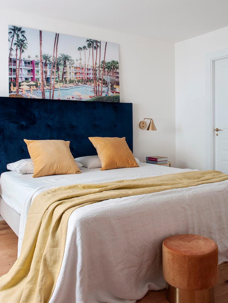 Dormitorio con cabecero tapizado en terciopelo azul con capitoné. Cojines y complementos mostaza. Dormitorio blanco y luminoso con toques de color. Apliques de pared dorados. Proyecto de reforma e interiorismo de R de Room.