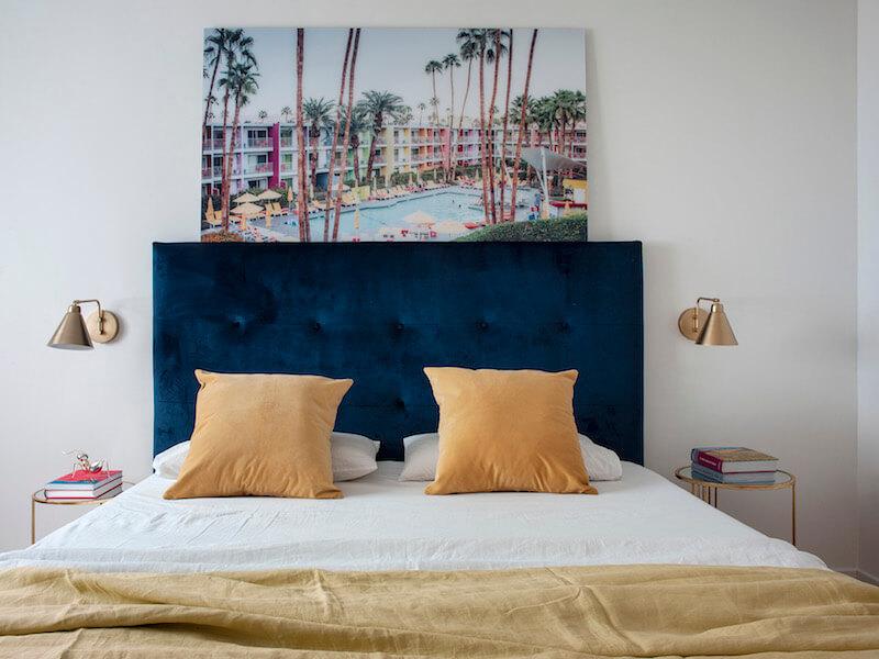 Dormitorio principal de vivienda en Madrid. Cabecero tapizado en terciopelo azul con capitoné. Cojines y complementos mostaza. Dormitorio blanco y luminoso con toques de color. Apliques de pared dorados. Cuadro de gran formato. Proyecto de reforma e interiorismo de R de Room.