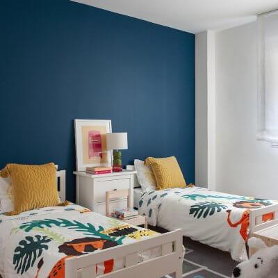 Dormitorio infantil de vivienda en Madrid. Pared del cabecero pintada en color azul pato. Colchas con estampado de animales y cojines mostaza. Cuarto de niños. Proyecto de reforma e interiorismo de R de Room.