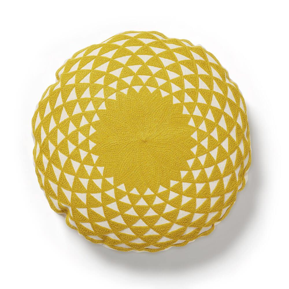 R DE ROOM cojín circular con relleno de color mostaza con detalles en blanco.