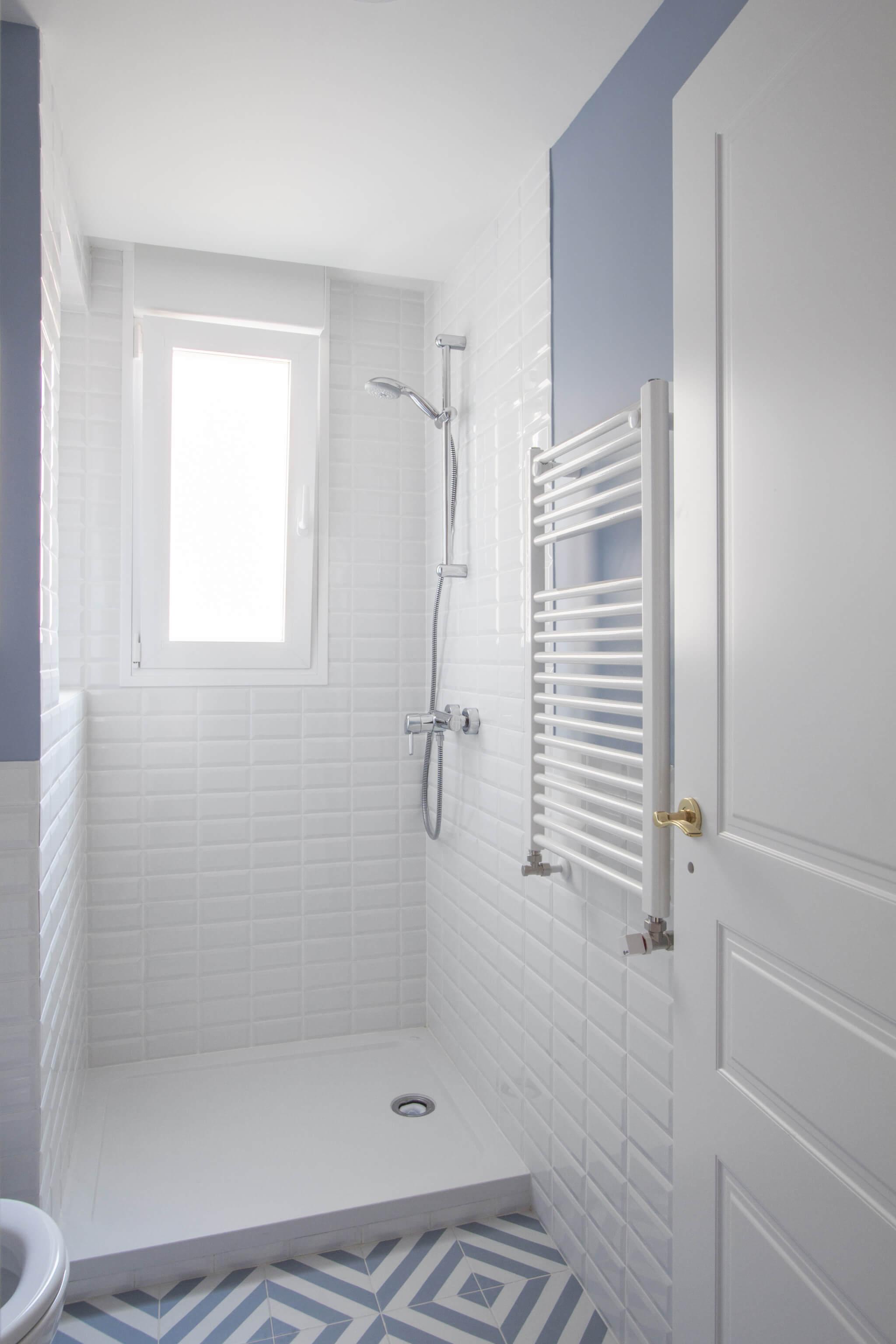 Baño con ducha en Madrid. Zócalo de azulejo metro blanco y pared pintada en color azul. Baldosa con estampado blanco y azul. Puerta blanca plafonada con tiradores dorados. Mueble de baño Hemnes de IKEA. Proyecto de reforma e interiorismo de R de Room.
