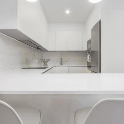 Proyecto de reforma en Chamberí (Madrid) de R de Room. Cocina abierta con barra. Frente de mármol blanco Calacatta