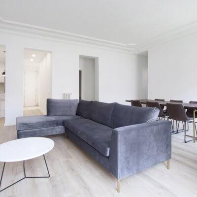 Proyecto de reforma en Chamberí (Madrid) de R de Room. Salón minimalista con cocina abierta. Molduras. Sofá gris. Espejo dorado.