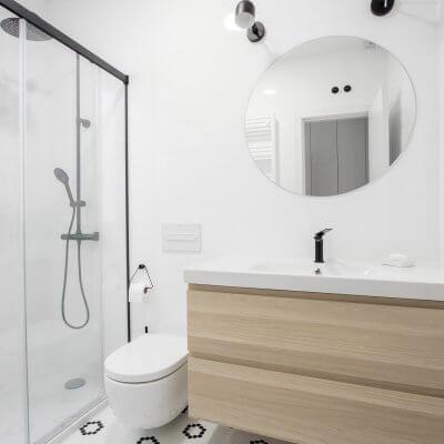 Proyecto de reforma en Chamberí (Madrid) de R de Room. Baño en blanco y negro. Suelo teselas Hisbalit. Grifería, mampara y focos negros.