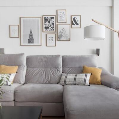 Interiorismo de vivienda_estar comedor-sofá gris-ambiente cálido-collage de cuadros