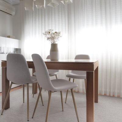 Interiorismo de vivienda_estar comedor-sofá gris-ambiente cálido-mesa de comedor-sillas tapizadas-sillas grises.