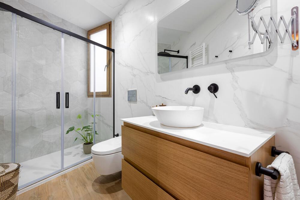 Elegante baño con mármol en las paredes y azulejo porcelánico efecto madera en el suelo combinado con mueble de madera. Proyecto de R de Room.
