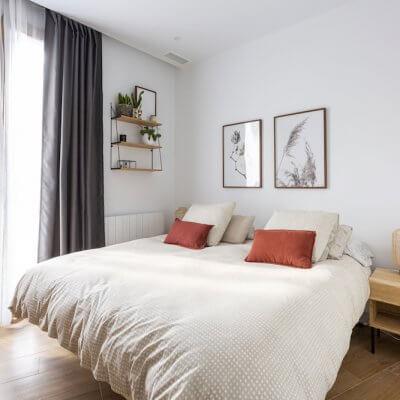 Dormitorio principal sencillo y acogedor donde los toques de madera de las mesitas y la estantería son los protagonistas. Proyecto de R de Room.