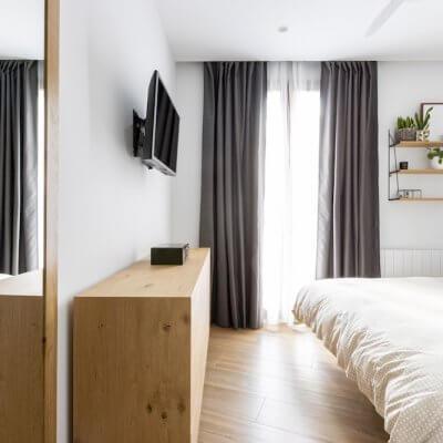 Dormitorio principal sencillo y acogedor donde los toques de madera de las mesitas, la cómoda y la estantería son los protagonistas. Proyecto de R de Room.