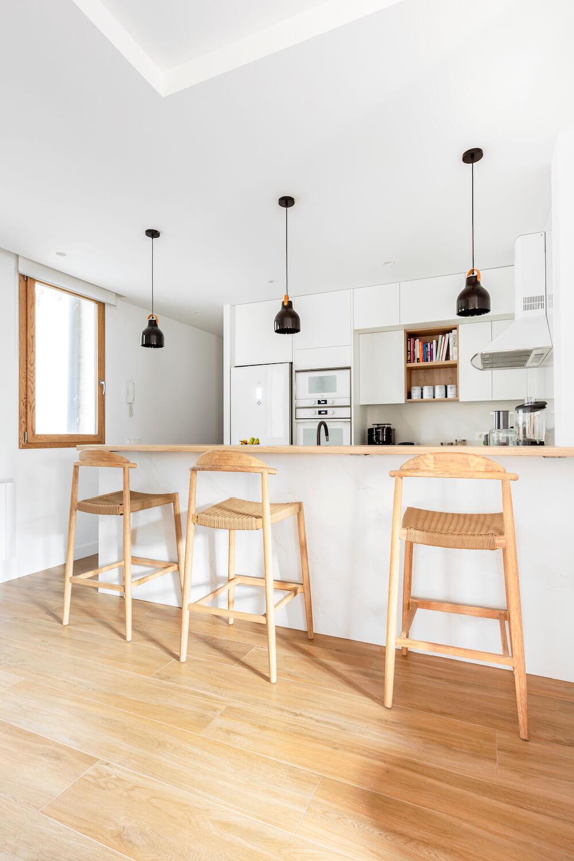 Barra en cocina abierta. Predomina el blanco con toques de madera. La encimera y los taburetes son el toque cálido perfecto para esta casa. Proyecto de R de Room.