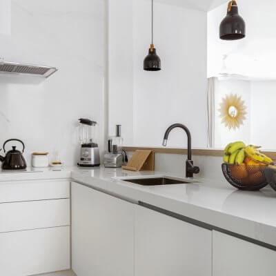 Cocina blanca con península abierta al salón. Detalles negros en grifo, lámparas y decoración. Proyecto de R de Room.