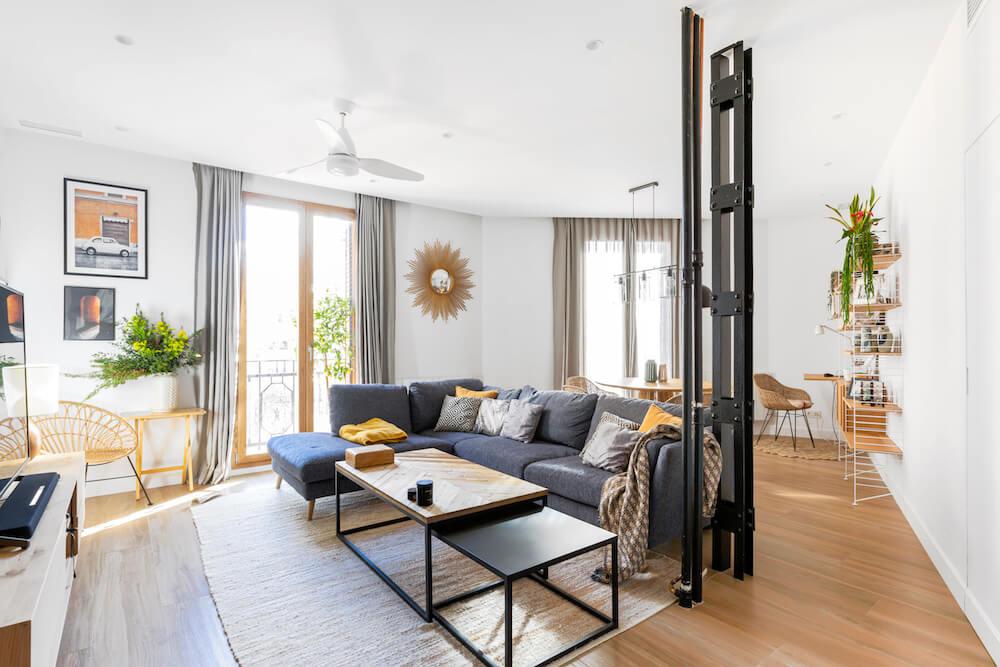 Salón-comedor con interiorismo de inspiración industrial y detalles retro. Tiene incorporada una zona de trabao resuelta con una estantería modular String. Proyecto de R de Room.