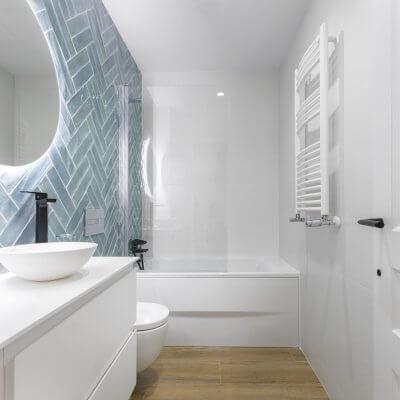 Azulejos azules esmaltados colocados a doble espiga y espejos circulares retroiluminados. Los grifos negros son la guinda del pastel para un baño perfecto. Proyecto de R de Room.