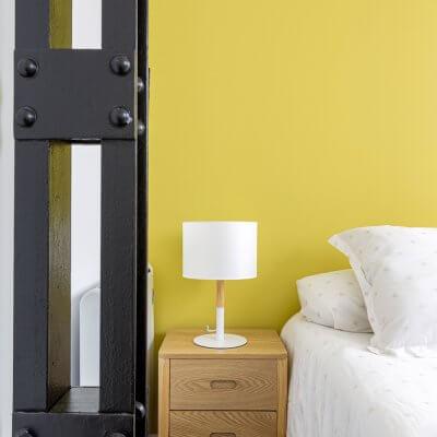 Sencillo pero efectivo dormitorio para invitados. Mesitas de madera, ropa de cama neutra y pared pintada en amarillo. Proyecto de R de Room.