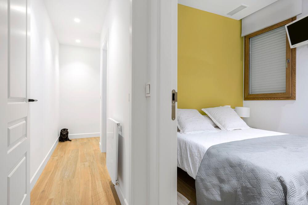 Sencillo pero efectivo dormitorio para invitados. Mesitas de madera, ropa de cama neutra y pared pintada en amarillo. Vista desde el pasillo. Proyecto de R de Room.