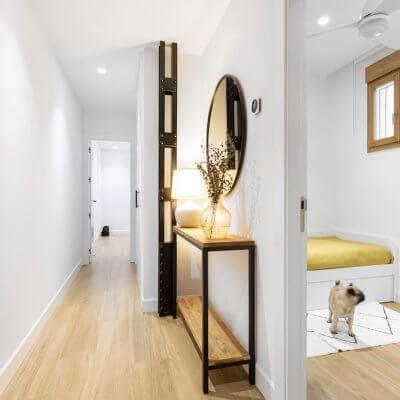 Vista del recibidor decorado con estilo industrial y del dormitorio para invitados. Proyecto de R de Room.