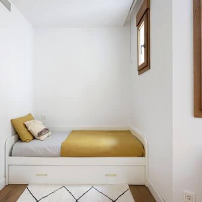 Dormitorio para invitados con cama nido y sillón Acapulco de ratán. Detalle con alfombra bereber. Proyecto de R de Room.