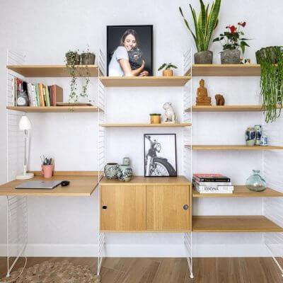 Sistema de estantería modular String con escritorio incorporado. Acabados roble y blanco. Proyecto de R de Room.