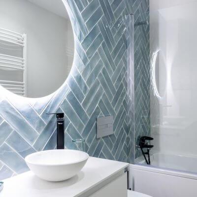 Azulejos azules esmaltados colocados a doble espiga y espejos circulares retroiluminados. Los grifos negros son el toque perfecto. Proyecto de R de Room.