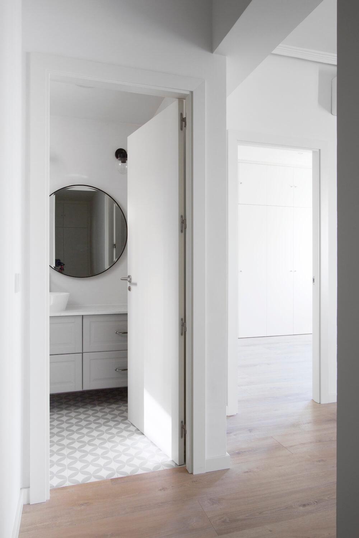 Vista al dormitorio principal con acceso al baño de cortesía en tonos grises. Proyecto de R de Room.