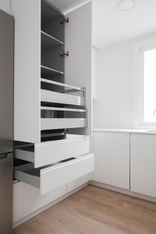 Cocina pequeña con gran capacidad de almacenamiento y acabados en blanco. Proyecto de R de Room.