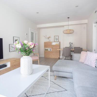 Salón con colores claros, madera y toques rosas. Proyecto de R de Room.