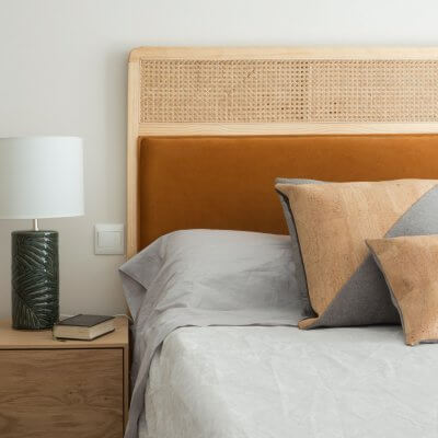 Dormitorio con mesitas de noche de madera y cabecero de rejilla y terciopelo caldera. Proyecto de R de Room.
