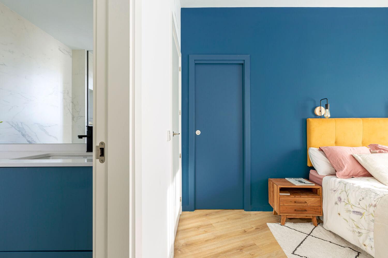 Dormitorio principal. Pared de cabecero azul. Vista con baño en suite. Proyecto de R de Room.