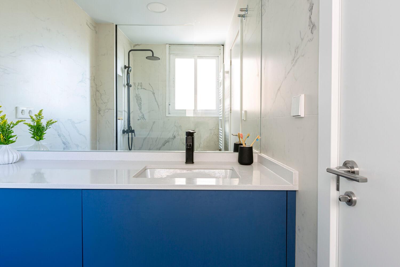 Baño en suite. Mármol blanco y mueble a medida azul. Proyecto de R de Room.