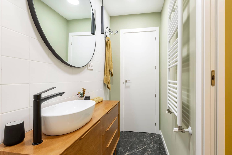 Baño blanco, verde, amarillo y negro. Mueble de lavabo aparador mid-century. Proyecto de R de Room.