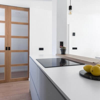 Cocina abierta con zona de lavadero. Puertas de madera. Proyecto R de Room.