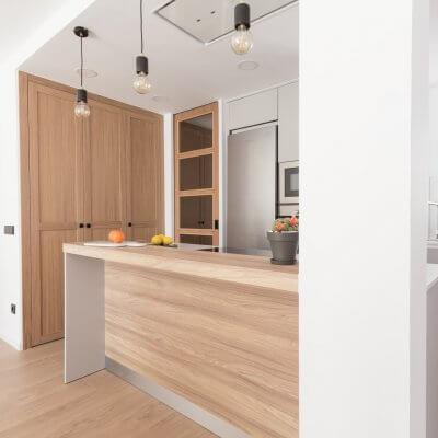 Cocina abierta gris claro y madera. Puertas con cuarterones. Proyecto R de Room.
