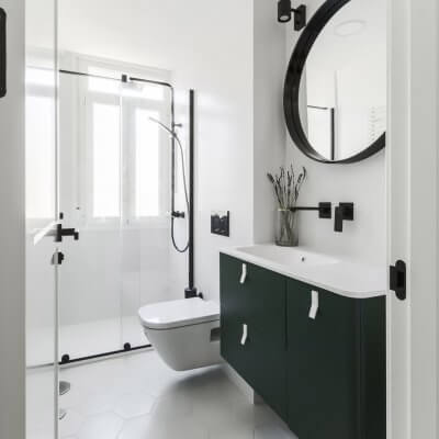 Baño principal con mueble verde y toques negros. Proyecto R de Room.