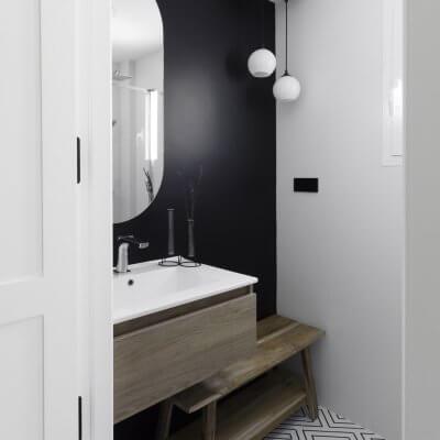 Baño de cortesía. Pintura negra y azulejo geométrico en b&n. Proyecto R de Room.