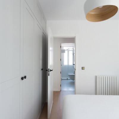 Carpintería interior con cuarterones en gris y blanco. Manillas y pomos negros. Vista hacia el baño principal. Proyecto R de Room.