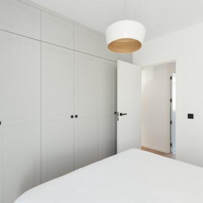 Carpintería interior con cuarterones en gris y blanco. Manillas y pomos negros. Proyecto R de Room.